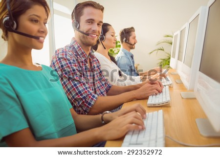 Portrait of a smiling businessman working with colleagues in a call centre - stock photo