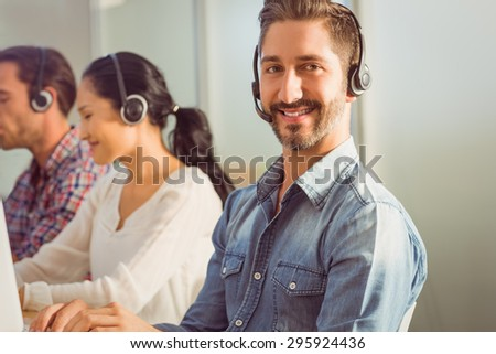 Portrait of a smiling businessman working with colleagues in a call centre