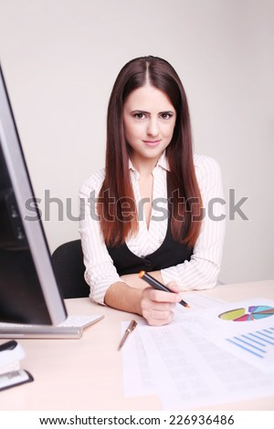 Portrait of a smiling businesswoman at office desk with a computer  - stock photo
