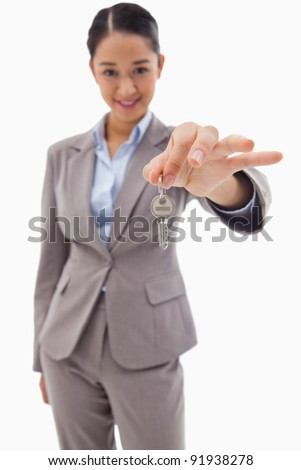 Portrait of a smiling businesswoman holding a key against a white background - stock photo