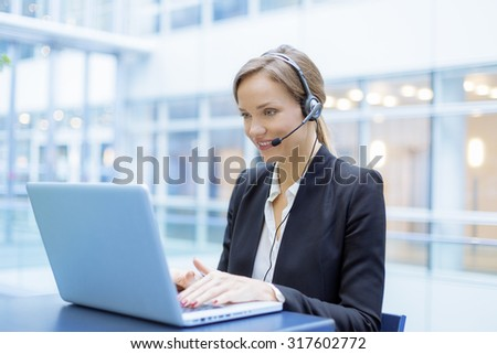 Portrait of a smiling Businesswoman using a head set