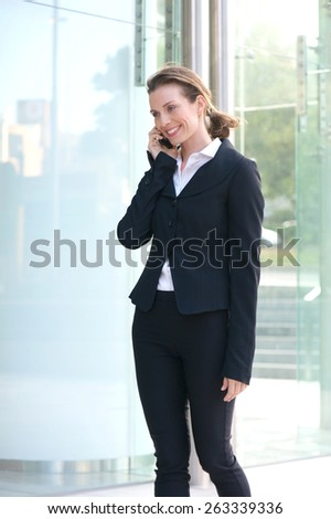 Portrait of a smiling businesswoman walking outside with cell phone - stock photo