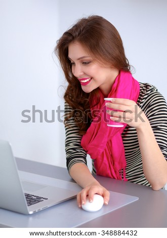 Portrait of a smiling businesswoman with coffee cup in front laptop