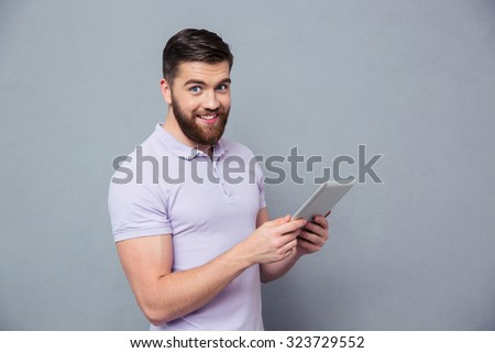 Portrait of a smiling casual man holding tablet computer and looking at camera over gray background - stock photo