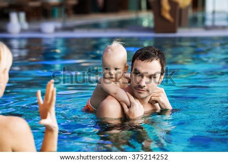 Portrait of a smiling charming 1 year child in the classroom in a swimming pool - stock photo