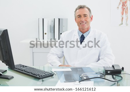 Portrait of a smiling confident male doctor sitting at desk in medical office - stock photo