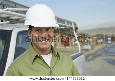 Portrait of a smiling construction worker in hardhat standing next to truck on construction site - stock photo