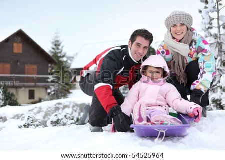 Portrait of a smiling couple and a little girl sledding - stock photo