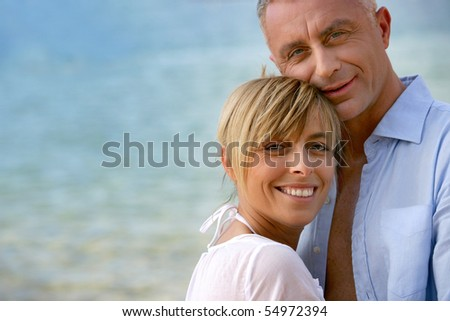 Portrait of a smiling couple at the beach - stock photo