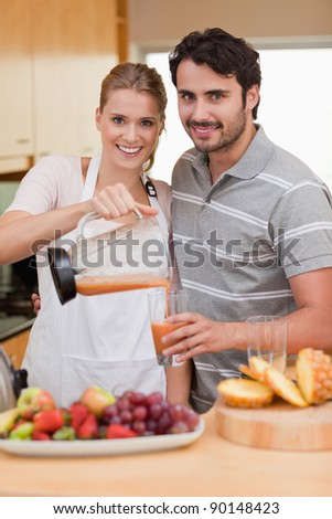 Portrait of a smiling couple drinking fruits juice in their kitchen