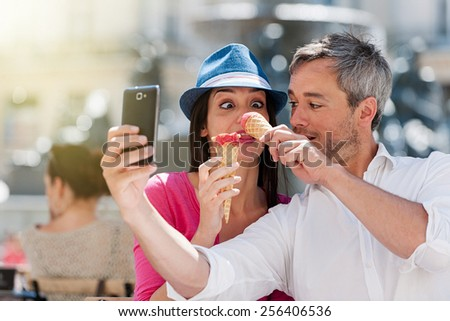 Portrait of a smiling couple eating ice cream and having fun in the city. The grey hair man with a beard is taking a selfie with phone. they make funny faces - stock photo