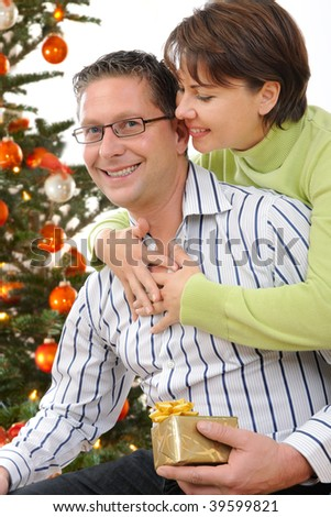 Portrait of a smiling couple holding gifts at Christmas tree - stock photo
