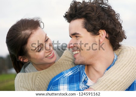 Portrait of a smiling couple hugging outdoors - stock photo