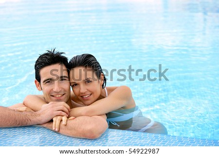Portrait of a smiling couple leaning on a poolside