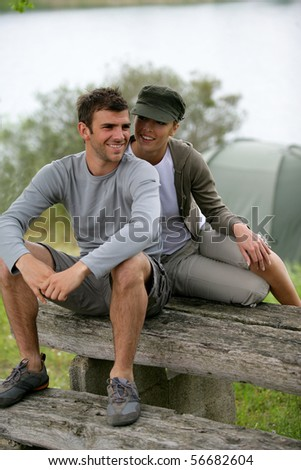 Portrait of a smiling couple of hikers sitting on a table - stock photo