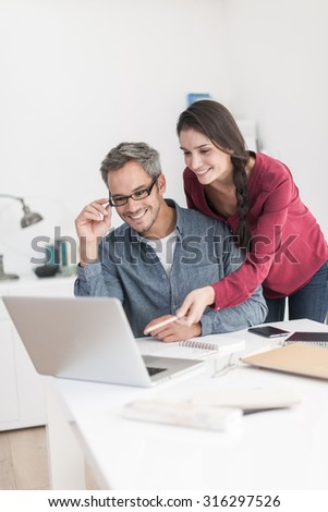 Portrait of a smiling couple planning their next trip, the grey hair man with beard and glasses is sitting at the table while his wife is leaning over his shoulder showing him an idea on the laptop