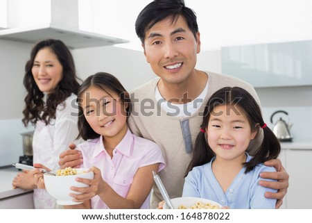Portrait of a smiling couple with happy two daughters having breakfast in the kitchen at home - stock photo