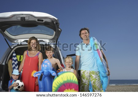 Portrait of a smiling couple with three children at beach by car - stock photo