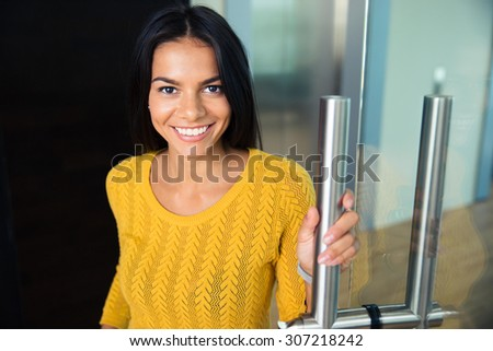 Portrait of a smiling cute businesswoman standing in office and looking at camera