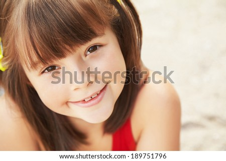 Portrait of a smiling cute little girl. child on vacation - stock photo