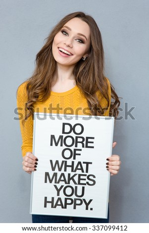Portrait of a smiling cute woman holding board with text: do more of what makes you happy over gray background - stock photo