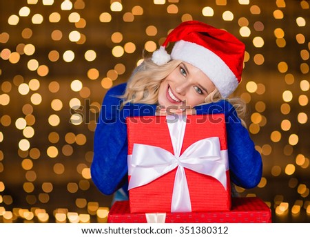 Portrait of a smiling cute woman leaning on present box over holidays lights background - stock photo