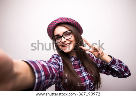 Portrait of a smiling cute woman making selfie photo on smartphone isolated on a white background - stock photo