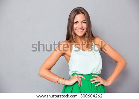 Portrait of a smiling cute woman standing over gray background and looking at camera - stock photo