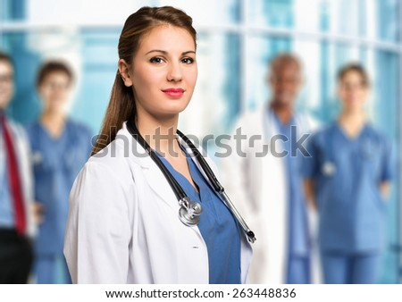 Portrait of a smiling doctor in front of a group of colleagues - stock photo