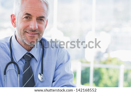 Portrait of a smiling doctor in his bright office - stock photo