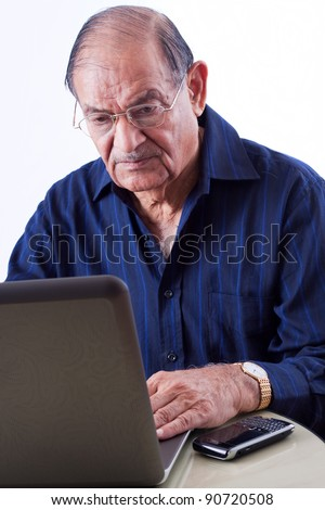 Portrait of a smiling elderly East Indian businessman on his computer laptop - stock photo