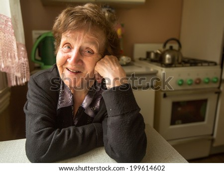 Portrait of a smiling elderly woman in her house. - stock photo