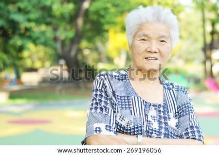 Portrait of a smiling elderly woman in public park - stock photo