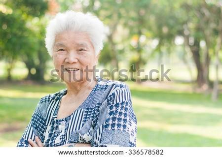 Portrait of a smiling elderly woman in public park - stock photo