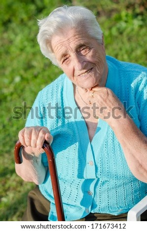 Portrait of a smiling elderly woman outdoor relaxing - stock photo
