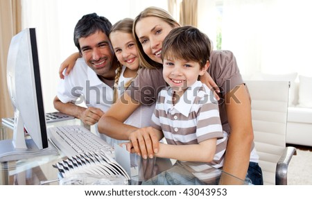 Portrait of a smiling family at a computer in the living-room - stock photo