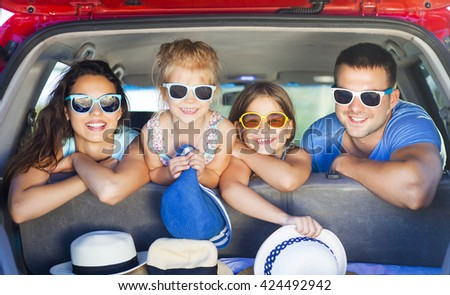 Portrait of a smiling family with two children at beach in the car. Holiday and travel concept - stock photo