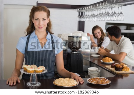 Portrait of a smiling female cafe owner with sweet snacks and couple at counter in the coffee shop - stock photo