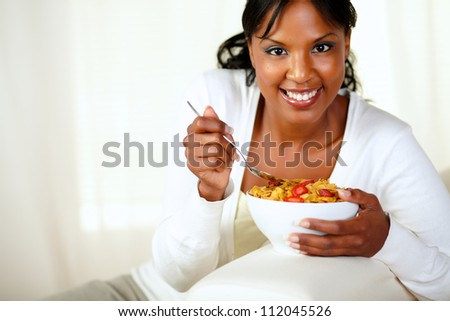 Portrait of a smiling female looking at you and having healthy breakfast while is sitting on sofa at home indoor. with copyspace - stock photo
