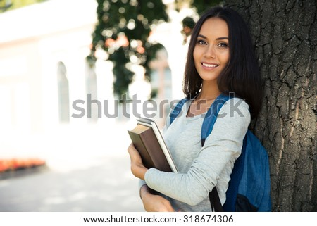 Portrait of a smiling female student standing with backpack and books outdoors - stock photo