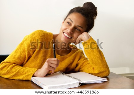 Portrait of a smiling female student thinking with with pen and paper - stock photo
