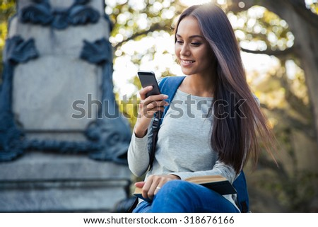 Portrait of a smiling female student using smartphone outdoors