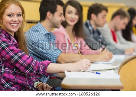 Portrait of a smiling female with other students writing notes in a row at the college lecture hall