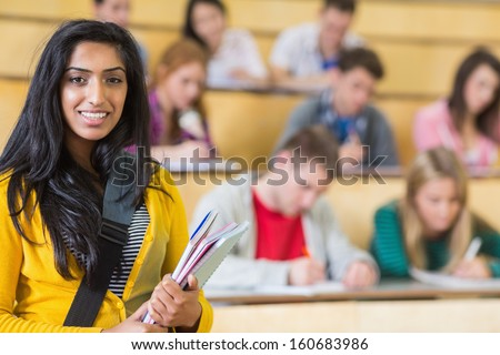 Portrait of a smiling female with students sitting at the college lecture hall - stock photo