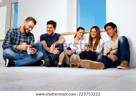 Portrait of a smiling friends sitting on the floor and looking at smartphone - stock photo