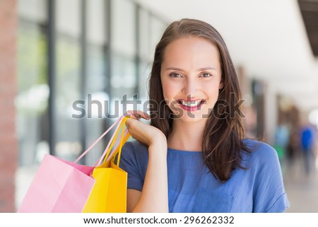 Portrait of a smiling girl holding shopping bags - stock photo