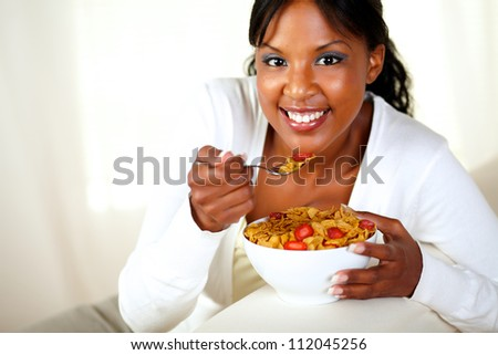 Portrait of a smiling girl looking at you and having healthy breakfast while is sitting on sofa at home indoor. with copyspace - stock photo