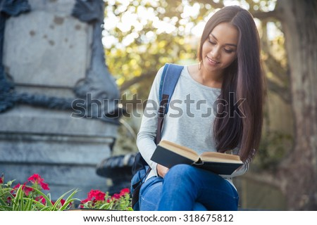 Portrait of a smiling girl reading book outdoors