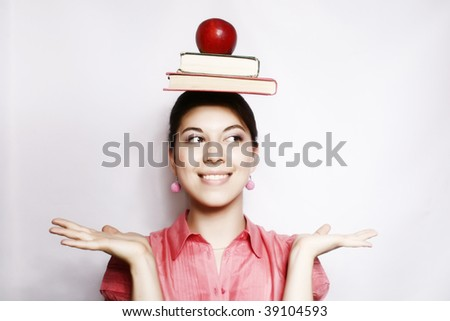 Portrait of a smiling girl with books on a head.