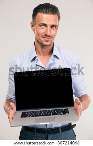 Portrait of a smiling handsome businessman showing blank laptop computer screen isolated on a white background - stock photo
